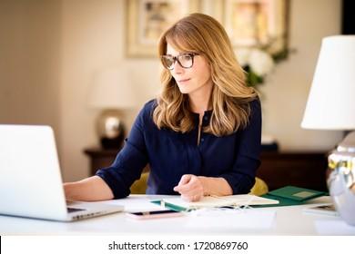 Porträtaufnahme von Frauen mittleren Alters, die in ihrem Heimbüro an ihrem Laptop arbeiten. Heimbüro.