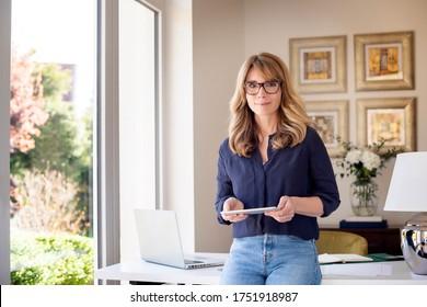 Porträtaufnahme einer Frau mittleren Alters, die digitale Tablette in der Hand hält, während sie die Kamera anschaut und lächelt. Lächelnde Geschäftsfrau, die von zu Hause aus arbeitet. Heimbüro.
