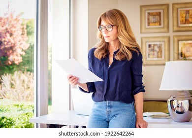 Portrait shot of middle aged woman holding a document in her hand while standing at desk and working. Home office.