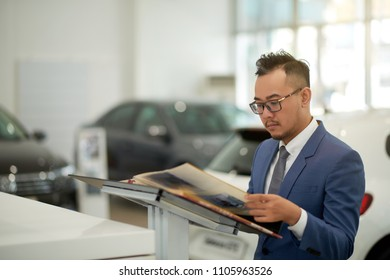 Portrait shot of middle-aged Asian man wearing elegant suit looking through catalog while waiting for automobile dealer at modern car showroom