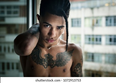 Portrait shot of a mixed black race model shirtless looking to the camera with an attractive and handsome face with a dreadlock hanging from his trendy haircut and putting his hand on his shoulder.
