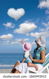 A portrait shot of mother and daughter sitting on a beach chair and looking at a heart-shaped cloud in the sky.