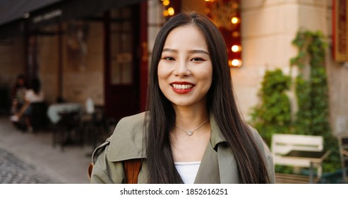 Portrait shot of pretty Asian happy young stylish woman looking and smiling to camera at nice street in town. Outdoors. Close up of beautiful cheerful female smile at cafe.
