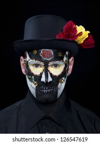 Portrait shot of a scary man wearing traditional sugar skull make-up with hat and roses against black background.