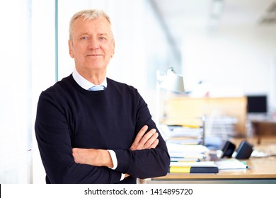 Portrait shot of senior businessman wearing causal clothes while standing with arms crossed in the office.