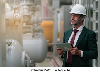 Portrait shot of senior engineer or management inspecting work in the boiler room in factory