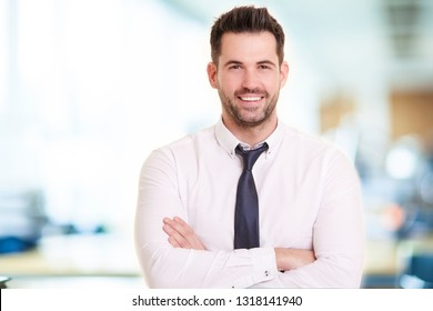 Portrait shot of smiling businessman wearing shirt and tie while standing with arms crossed in the office.