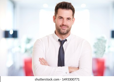 Portrait shot of smiling businessman wearing shirt and tie while standing in the office and smiling.