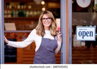 Portrait shot of smiling cafe owner businesswoman standing in the doorway with folded arms and waiting for her guest.