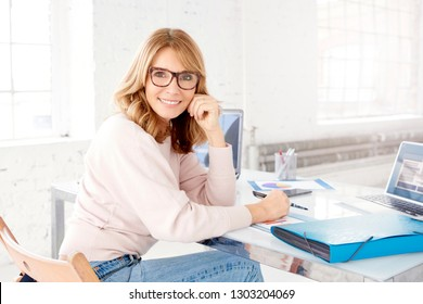 Portrait shot of smiling confident businesswoman wearing casual clothes while sitting at office desk and working.