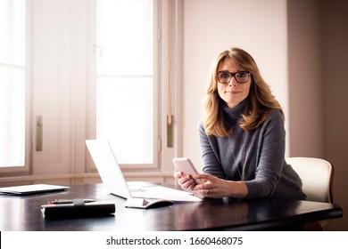 Porträtaufnahme einer lächelnden reifen Frau, die während ihres Schreibens am Schreibtisch hinter ihrem Laptop Kamera und Textnachrichten anschaut. Heimbüro.