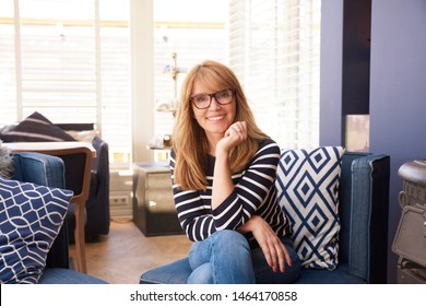 Portrait shot of smiling middle aged woman wearing casual clothes while sitting on sofa at home and relaxing.