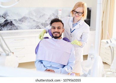 Portrait shot of smiling mixed-race patient sitting on dental chair and looking at camera while pretty stomatologist adjusting bib, interior of modern office on background