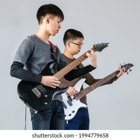 Portrait shot of two young teenage school friends playing music together. Professional junior guitarist and bassist playing electric guitar and bass guitar isolated with a white background