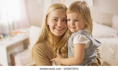 Portrait Shot of a Young Beautiful Mother Holding Her Little Cute Daughter In Her Arms. They Smile into the Camera.
