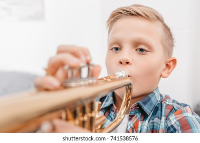 Portrait shot of young boy practicing playing trumpet