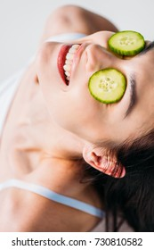 Portrait shot of young smiling woman with slices of cucumber on her eyes