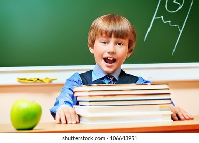 Portrait of a shouting schoolboy in a classroom.