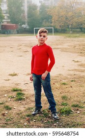 Portrait of a shy preteen boy in a red turtleneck and jersey in the open air