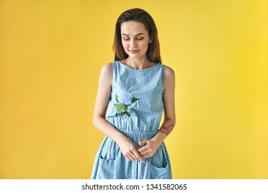 Portrait of shy smiling beautiful woman looking down on yellow studio background