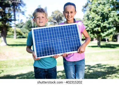 Portrait of siblings holding a solar panel in park