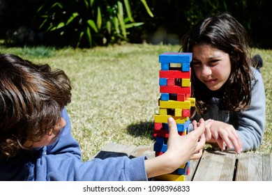 Portrait of siblings playing logical game with colorful bricks called 'jenga' lying on green grass in the backyard on sunny day.