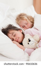 Portrait of siblings sleeping in a bedroom