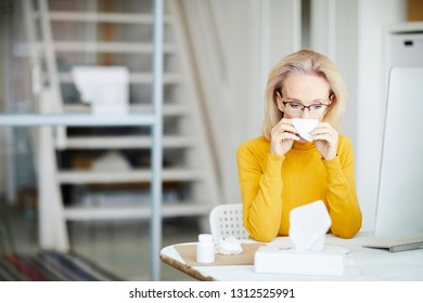 Portrait of sick adult woman blowing nose at workplace in office, copy space