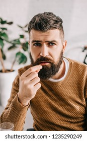 portrait of sick bearded man looking at camera and taking pill from illness