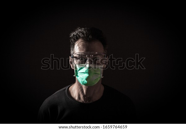 Portrait d'homme caucasien malade portant un masque médical. Concept du Coronavirus Covid-19. Arrière-plan noir