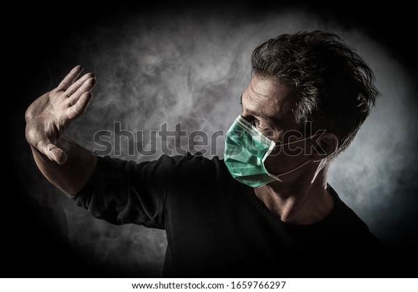Portrait d'homme caucasien malade portant un masque médical. Concept du Coronavirus Covid-19. Arrière-plan noir et fumée