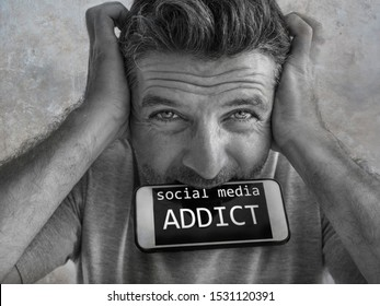 portrait of sick and crazy stressed man biting mobile phone screaming desperate and hysteric looking like a weirdo in internet and social media addiction concept isolated background