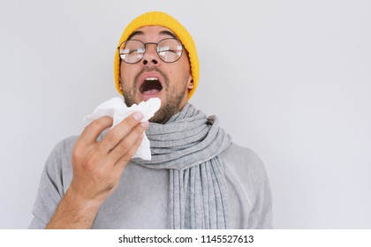 Portrait of sick handsome man wearing grey sweater, yellow hat and spectacles, blowing nose and sneeze into tissue. Male have flu, virus or allergy respiratory. Healthy, medicine and people concept