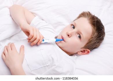 Portrait of sick little boy measuring body temperature
