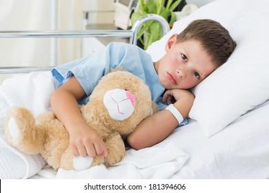 Portrait of sick little boy with teddy bear in hospital bed