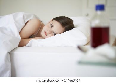 Portrait of sick little girl lying in bed