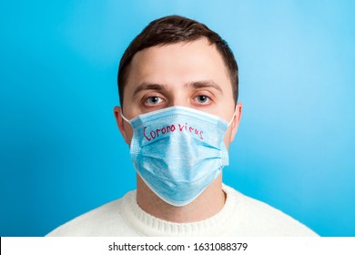 Portrait of a sick man wearing medical mask with coronavirus text at blue background. Coronavirus concept. Protect your health.