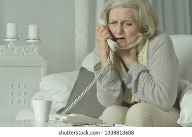 Portrait of sick mature woman calling doctor