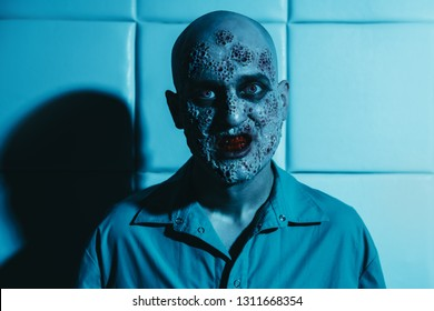 A portrait of a sick scientist after a failed experiment in the blue light. desperation, hopelessness. Horror, halloween.