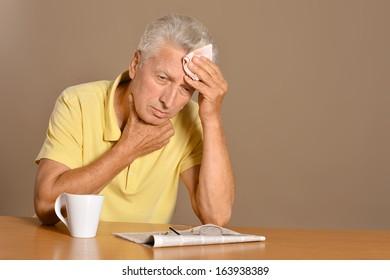 Portrait of a sick senior man on brown background