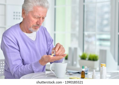 Portrait of sick senior man with pills posing