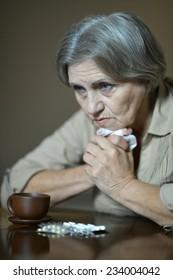Portrait of sick senior woman taking pills