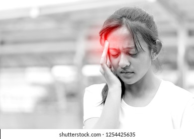 Portrait of Sick teenage girl Suffering from Head Migraine, Feeling Pressure And Stress. Healthcare and Pain. Stressed Exhausted Young Asian Woman Having Strong Tension or having a headache on city