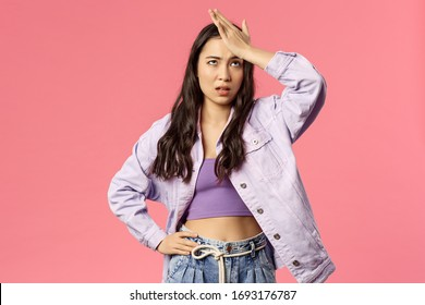 Portrait of sick and tired, annoyed young stylish girl taking care of new employee, facepalm, do eye roll and punch forehead sighing bothered, have lots of troubles, stand pink background