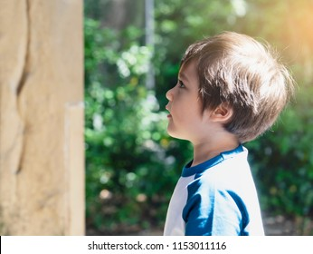 Portrait side view of cute little boy with curious face standing next to the old brick wall, Active kid looking up with intresting of some things an old wall at museum, Child learn and play