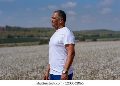 Portrait Side View Of Handsome Old Active Senior Man Outdoors. Sporty athletic elderly businessman on background of sky and cotton field. Senior farmer standing in meadow background.