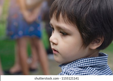 Portrait side view of littile boystanding alone with blurry back ground of peoples walking behind, Head shot of Active child looking around finding some one.