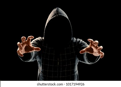 Portrait, silhouette of a man in a hood on a black background, his face is not visible. The concept of a criminal, incognito, mystery, secrecy, anonymity.