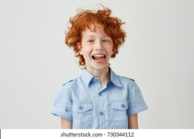 Portrait of silly little ginger boy in blue shirt with wild hair mowing eyes, smiling and showing tongue in camera,making funny faces.