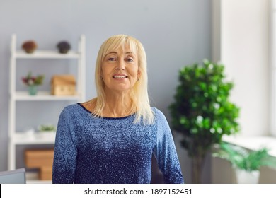 Portrait of a sincere and kind middle aged mature woman who is looking at the camera. Woman posing relaxed at home or in the office with a natural face and a confident smile.